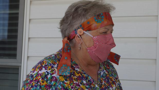 Rita Dovre dons one of the masks she sewed for the public health providers, including a headband with a button to attach the mask.