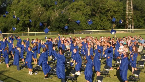 Minneota seniors toss their caps high in the air after the completion of the graduation ceremony Friday night.