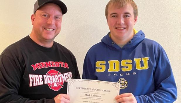 Mark Laleman, right, is presented with a $1,000 scholarship from the Minnesota Fire Service Foundation by his father, Brad Laleman, a member of the Minneota Fire Department.
