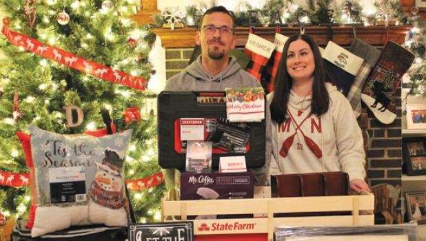 "Austin and Shannon Dritz pose in their home south of Taunton with some of the many prizes they received for winning the Mascot ""Battle of the Bulbs"" Christmas Lighting Contest this year. There were 29 entries to this year's contest."