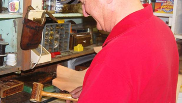 Dan Markell works on a leather handle for one of the trunks he is restoring.