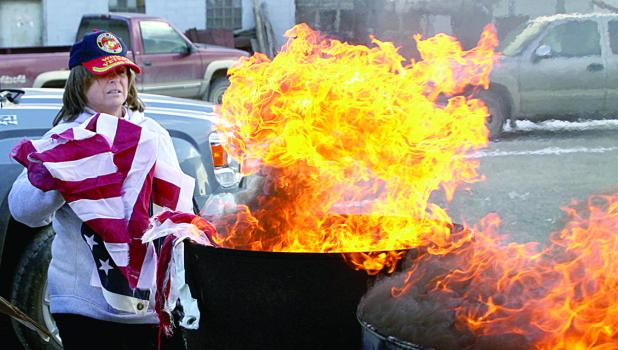 Pam Gregor helped burn the used flags.