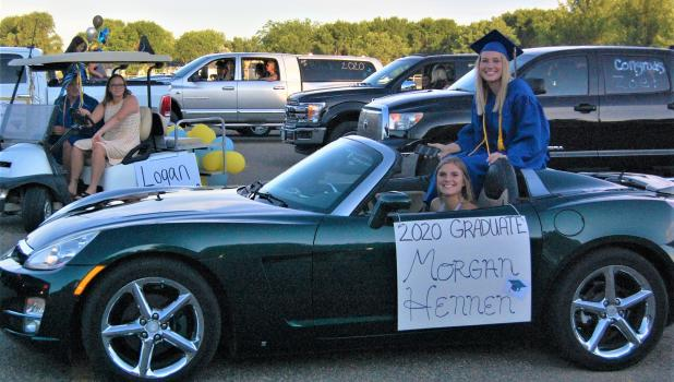 With classmates getting ready for the graduation parade, Morgan Hennen prepares to have her sister Abby chauffeur her through the streets of Minneota on Friday night.