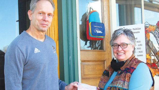 Joel Skillings, left, hands Minneota librarian Gail Perrizo a check to purchase children's books in a tribute to his late wife Jackie.