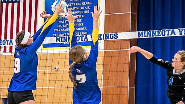 Abby Frie, left, and McKenna Yost go up for a block against CMCS on Tuesday night.