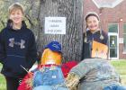 """Audyn Traen and Stella Gorecki with their scarecrow """"Farmers Jimmy and John""""."""