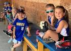 These kids waiting in the dugout to play a game enjoy wearing the Minneota colors during their Summer Rec games.